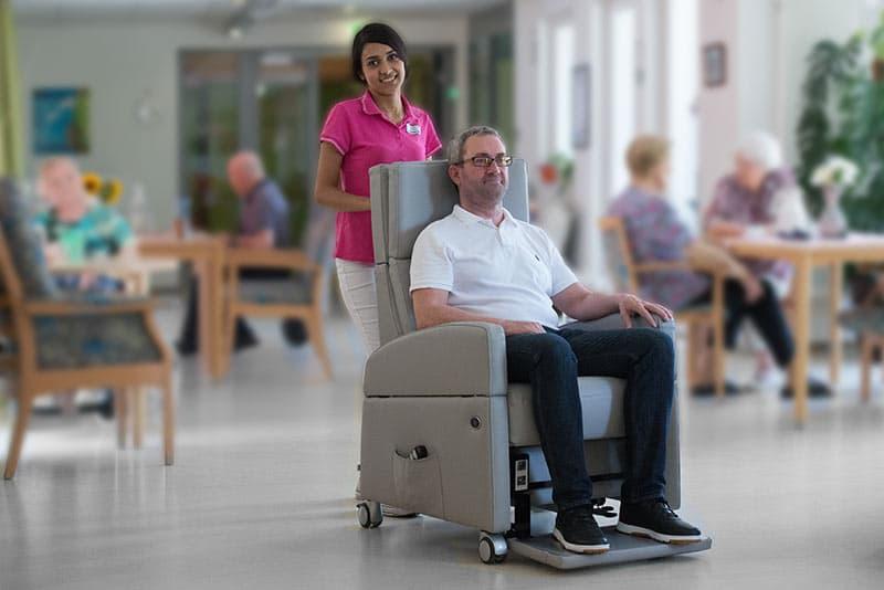 Mit dem Pflegesessel / Aufstehsessel mit Rollen mobil in der Senioren-Einrichtung.