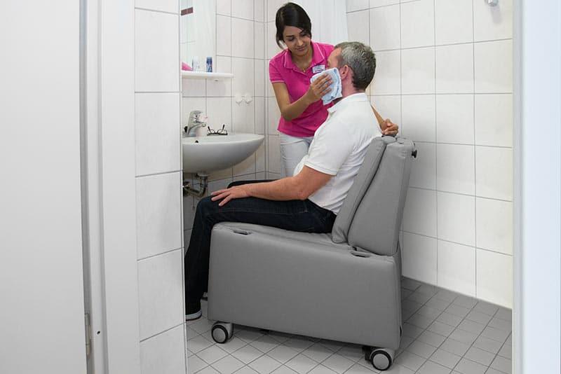 Aufstehsessel / Pflegesessel mit Rollen und Aufstehhilfe: Körperpflege im Sitzen mit entfernten Armlehnen.